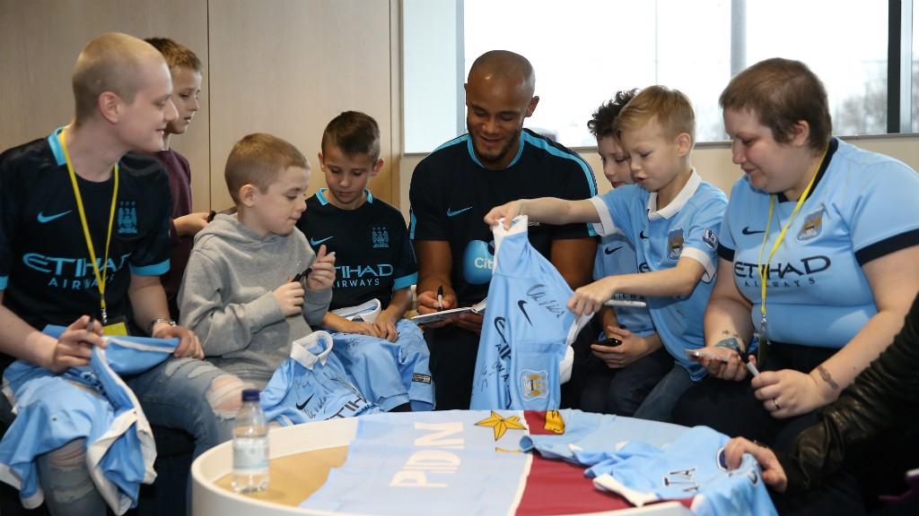 Vincent Kompany adds his signature to some lucky fans shirts.