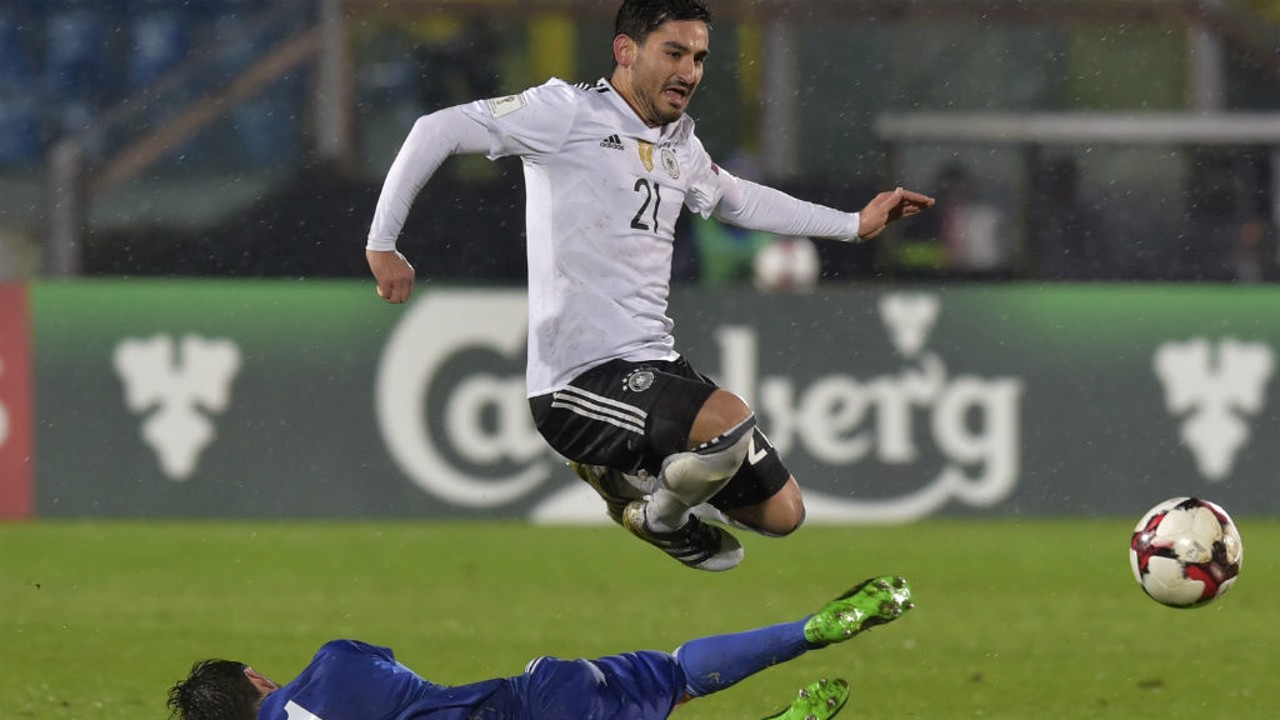 UP AND AT 'EM: Ilkay Gundogan hurdles a challenge by San Marino's Tommaso Zafferani during Germany's 8-0 win