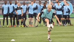Betsy Hassett does keepy-uppys watched on by the u18 squad
