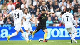 ATTACK: Swansea captain Leon Britton faces up to Sergio Aguero