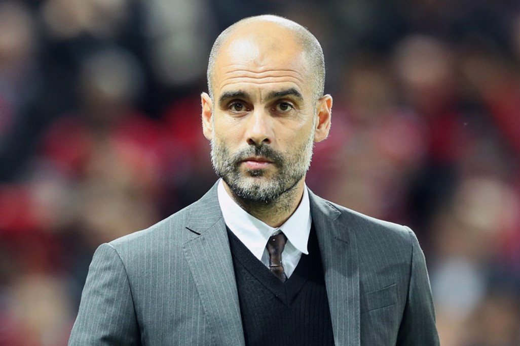 Pep Guardiola walks to his seat for the match
