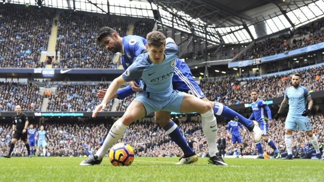 BATTLE: John Stones shepherds the ball out, under pressure from Diego Costa