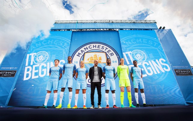 CENTRE STAGE: Pep Guardiola in front of the new Club badge, with players from across City teams in the new kit