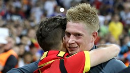ADORED: De Bruyne is hugged by a Belgium fan after another excellent performance