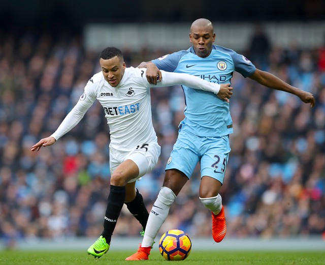 FIGHT: Fernandinho battles for position and the ball against Swansea.