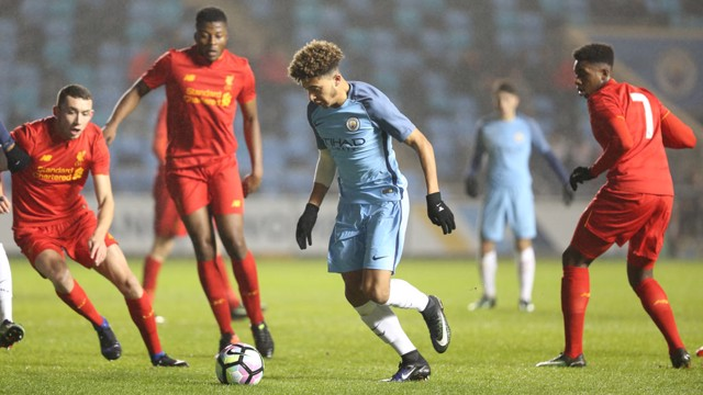 SURROUNDED: Jadon Sancho has another go at getting around a compact Liverpool defence