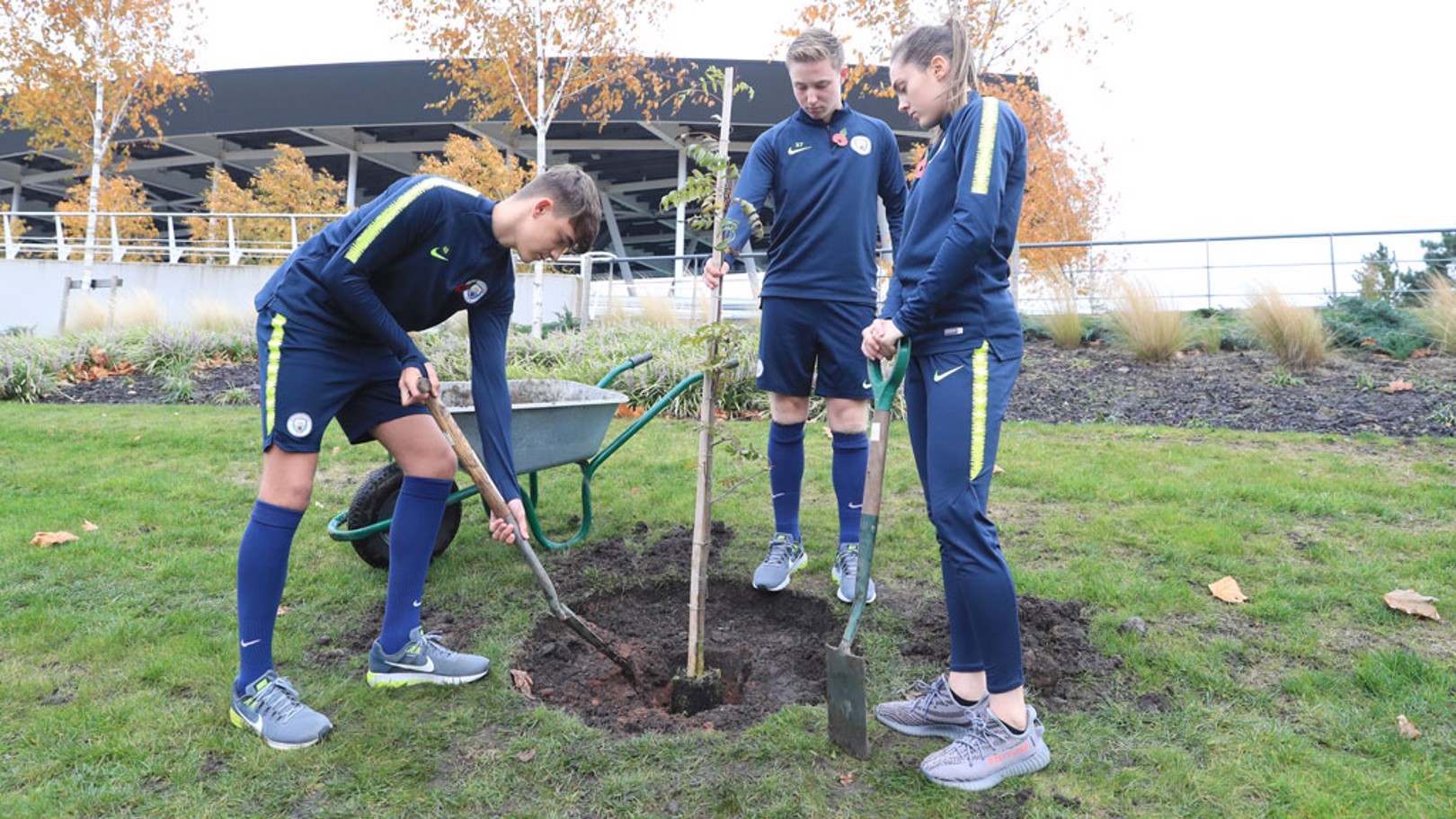 Academy players Harvey Griffiths, Tom Midfley and Katie Bradley plant the trees