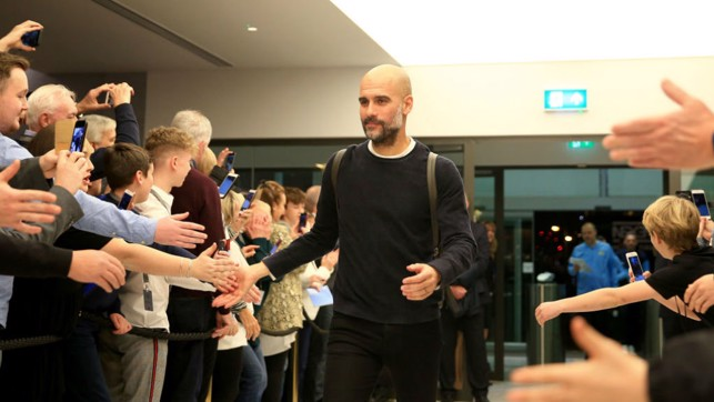 HI FIVE : Pep is greeted upon arrival at the Etihad Stadium