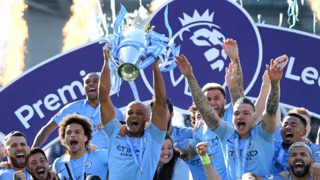 A LEAGUE APART : Kompany holds the Premier League trophy aloft after City's successful 2018/19 title defence