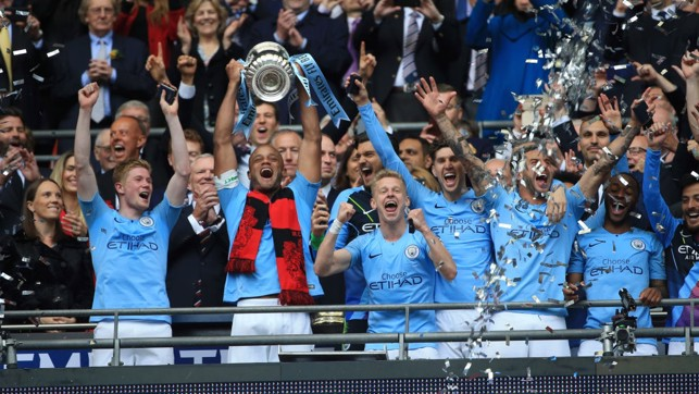 LIFTED : Kompany and the team celebrate their fourth piece of silverware this season
