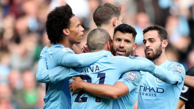 GIVE US A HUG : Sergio celebrates with his team-mates after his early strike