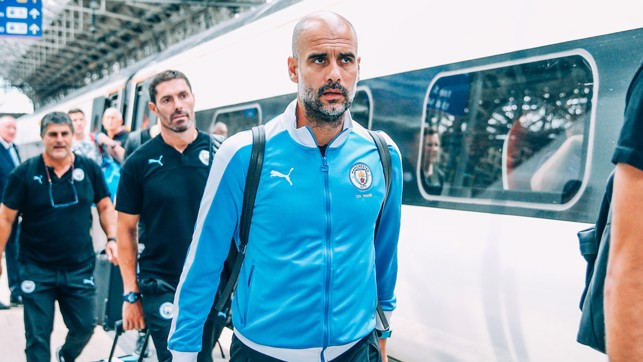 THE BOSS : Pep Guardiola prepares to board the train ahead of the journey to London