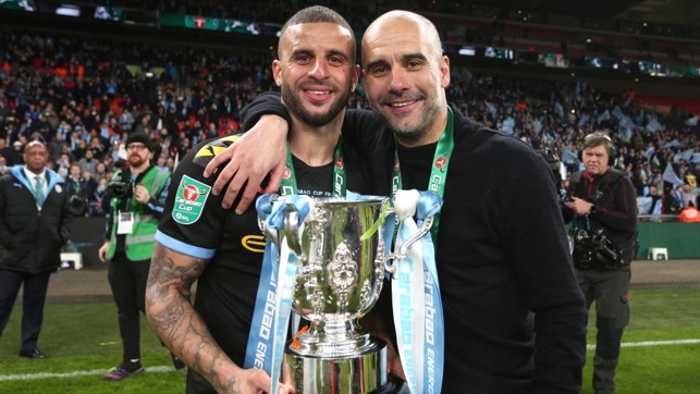 ALL SMILES : Walker and Guardiola strike a pose with the trophy.