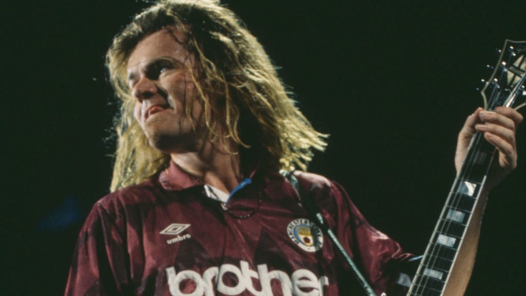 TRUE COLOURS : Billy on stage with the Cult wearing a City shirt