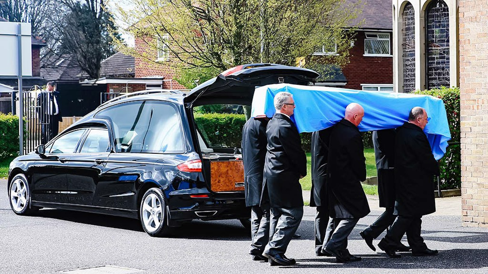 Bernard's coffin was draped in sky blue, adorned with lilies.