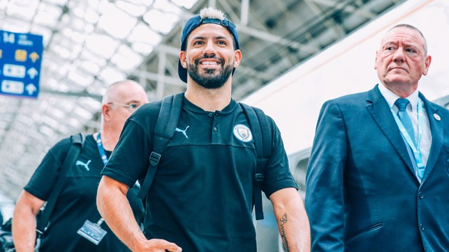HAT'S THE WAY TO DO IT : Sergio Aguero is all smiles as he prepares to board the train to London