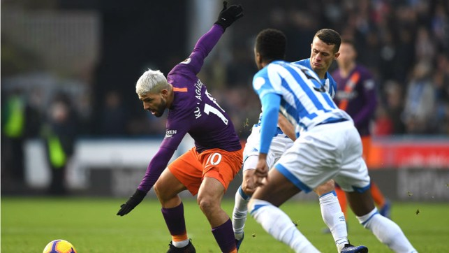 AT ARMS LENGTH : Sergio Aguero looks to shield the ball from the Huddersfield defence