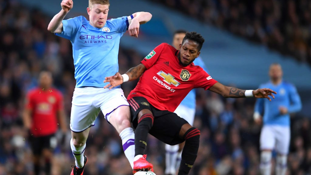 TUSSLE : De Bruyne challenges Fred for the ball in midfield_
