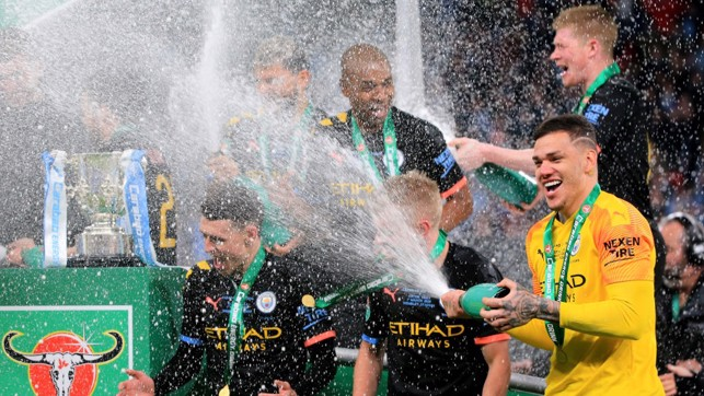 SAFE HANDS : Ederson showers Foden in some champagne.