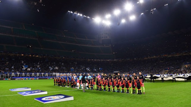 ALL LIT UP : The players line up at the San Siro ahead of kick-off