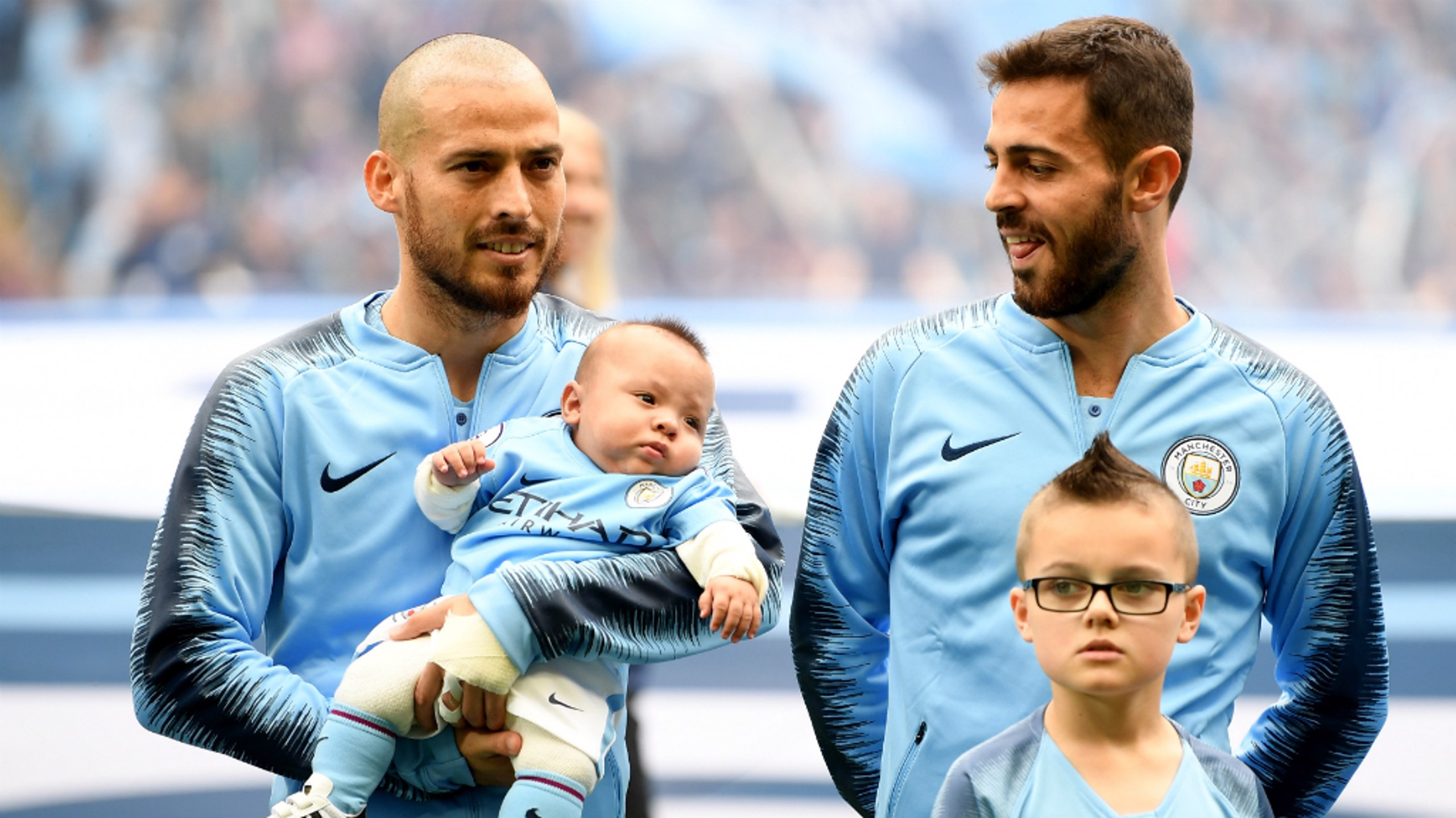 LITTLE BOY BLUE: David Silva cradles his son Mateo before kick-off