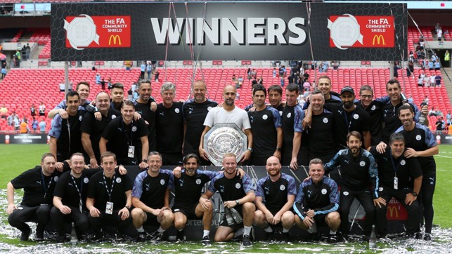 WINNING FORMULA : Pep Guardiola's staff pose with the latest trophy in their collection.
