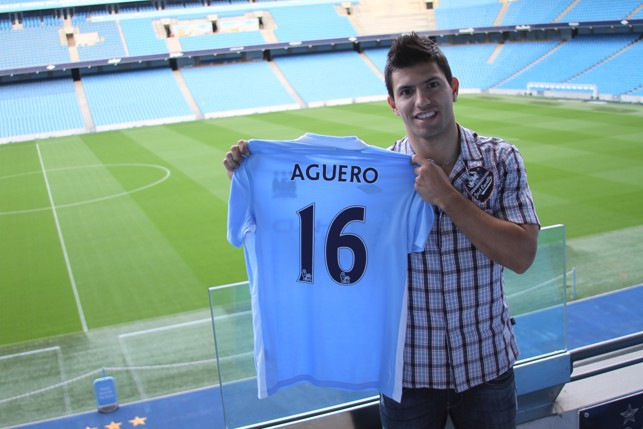 HAPPY TIMES : Aguero smiles as he poses with his new City shirt in 2011