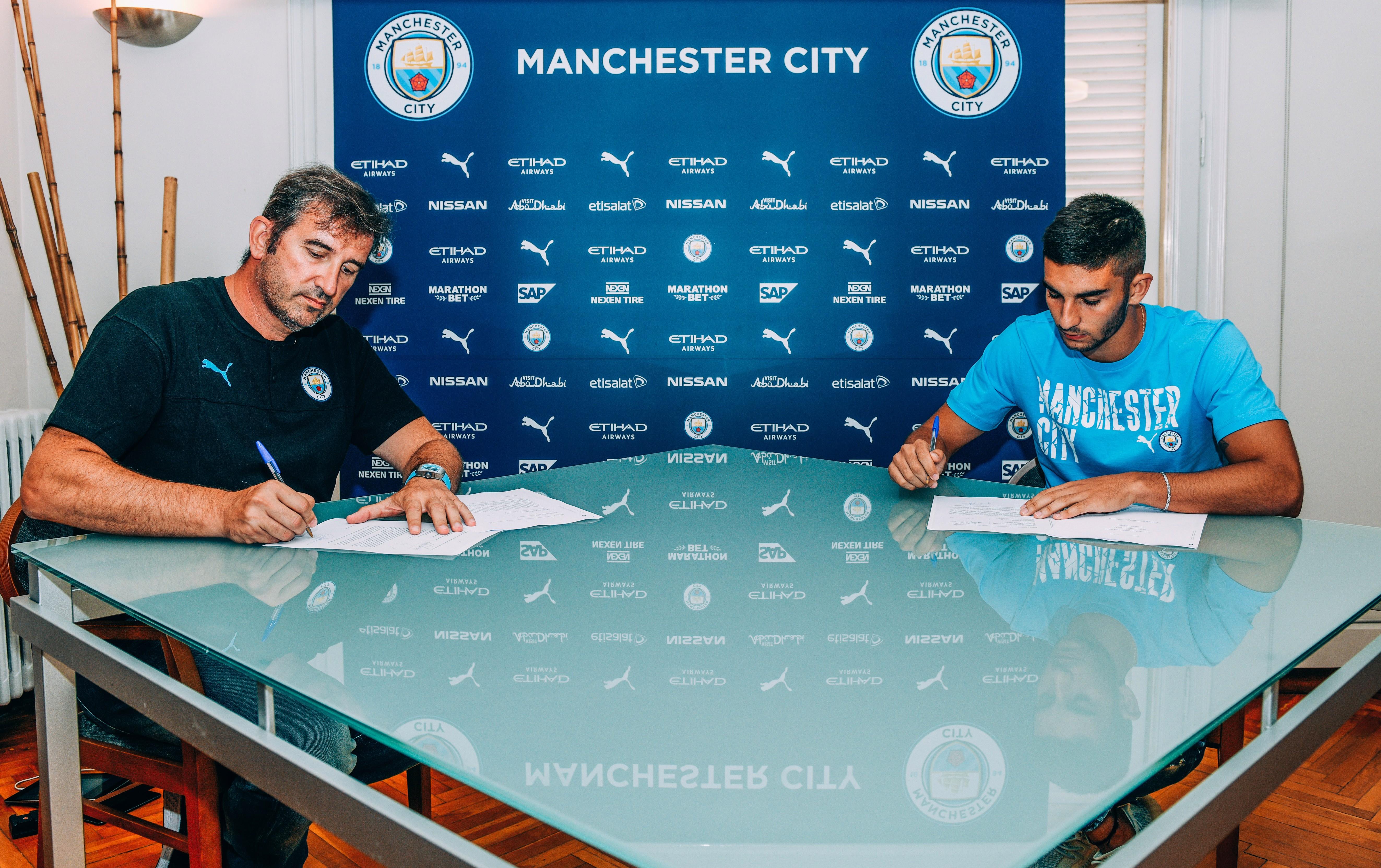 FIRMA. : Ferran Torres firma su contrato con el Manchester City junto a Ferran Soriano.
